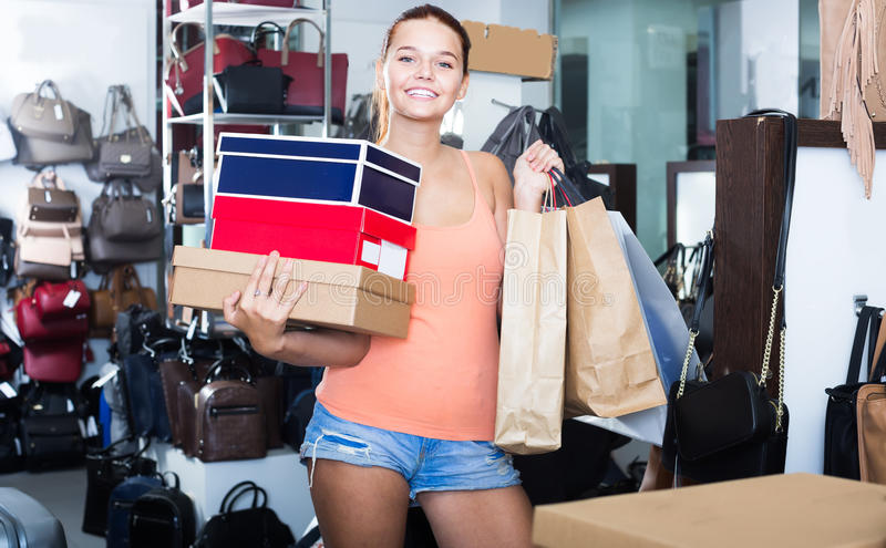 Happy teenager female holding boxes in shoes boutique. Happy teenager female holding boxes with chosen pairs in shoes boutique royalty free stock photos