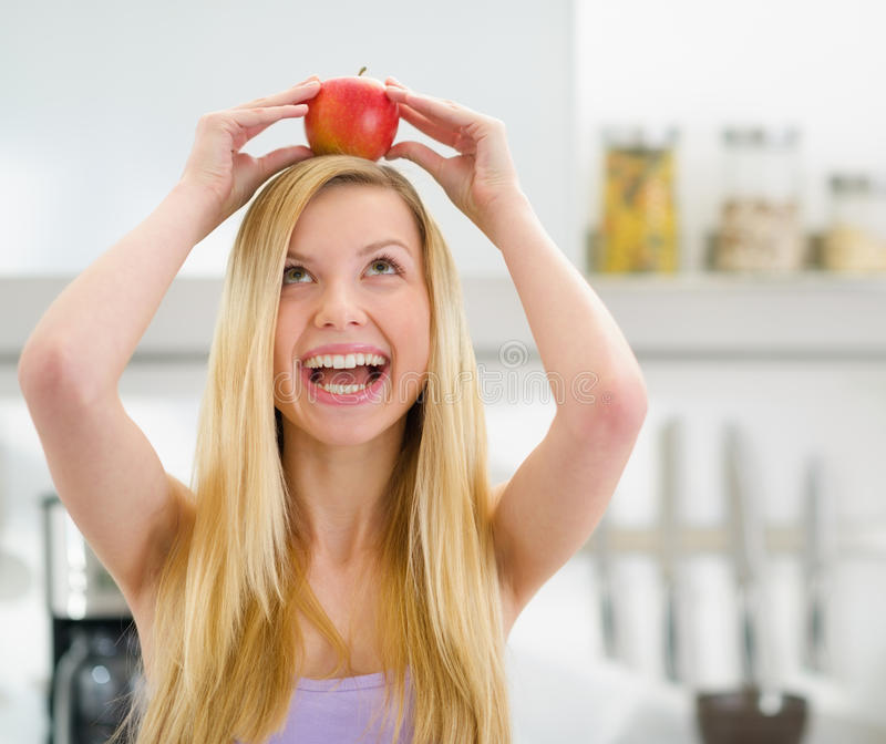 Happy teenager girl with apple on head in kitchen stock images