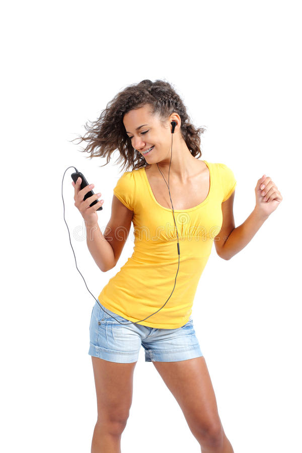 Happy teenager girl dancing and listening to the music. Isolated on a white background stock photo