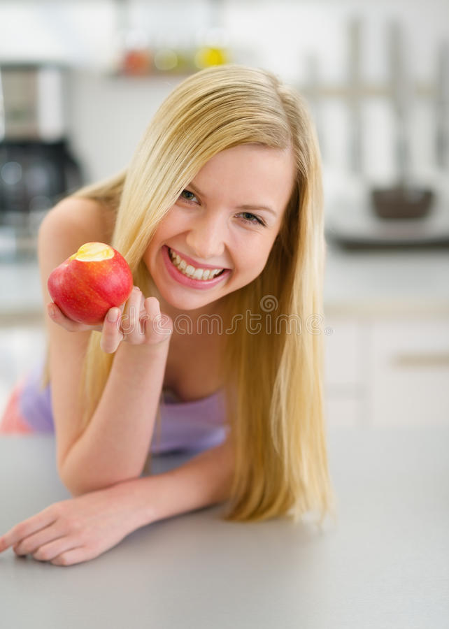 Happy teenager girl eating apple in kitchen stock photography