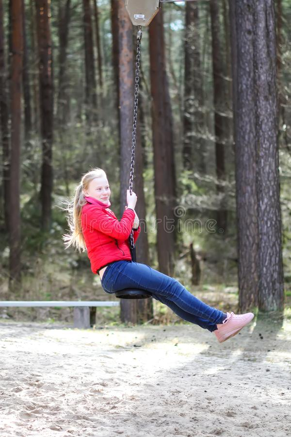 Happy teenager girl jumping with bungee in park. Happy blonde teenager girl jumping with bungee in park stock image
