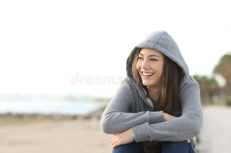 Happy teenager girl looking at side outdoors. Portrait of a happy teenager girl smiling and looking at side outside on the beach royalty free stock photo