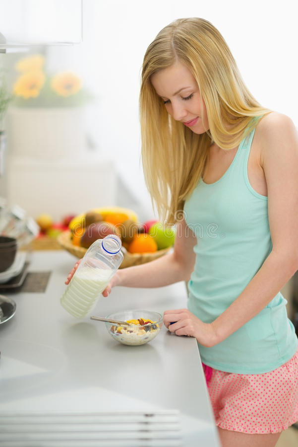 Happy teenager girl making breakfast in kitchen. Happy teenager girl with blond hair making breakfast in kitchen royalty free stock photos