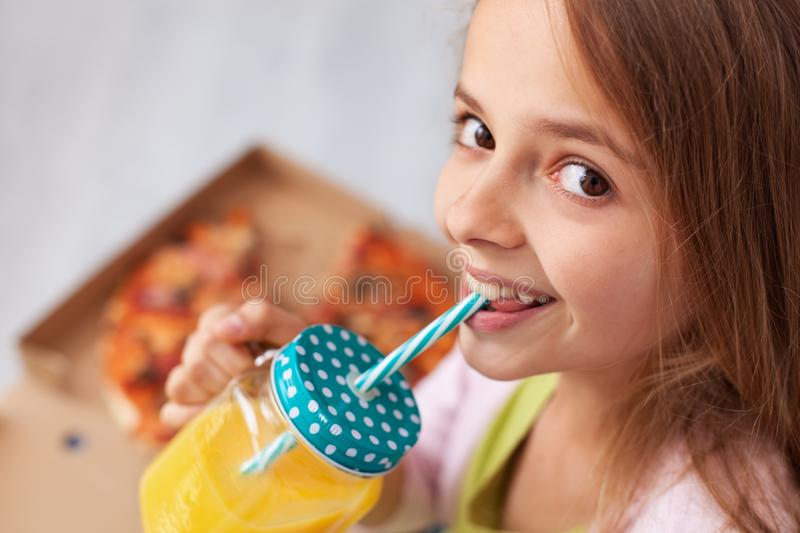 Happy teenager girl sitting on the floor with a box of pizza sip stock image