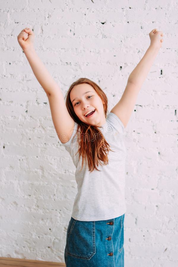 Happy teenager girl on the white background of the wall. Portrait smile young smiling hair isolated beautiful cheerful person people female beauty positive red stock photos