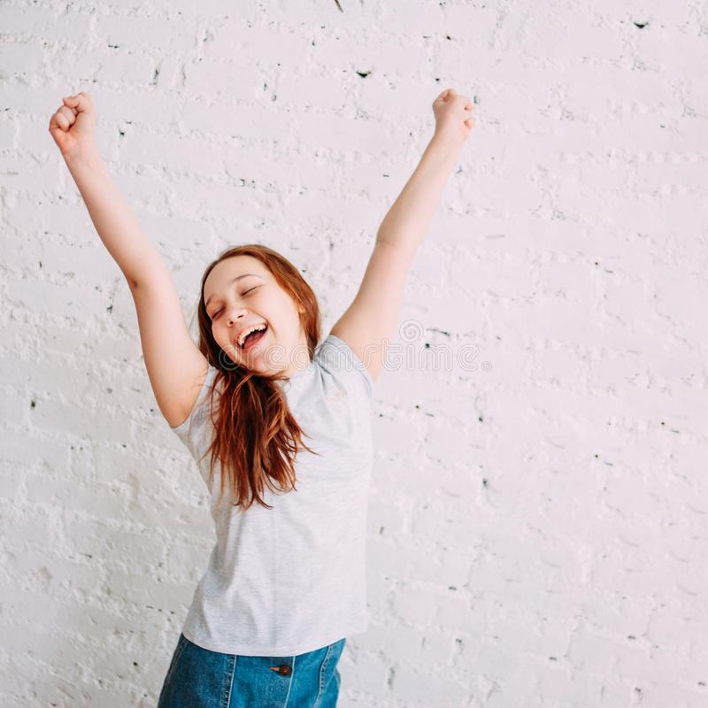 Happy teenager girl on the white background of the wall. Portrait smile young smiling hair isolated beautiful cheerful person people female beauty positive red royalty free stock images
