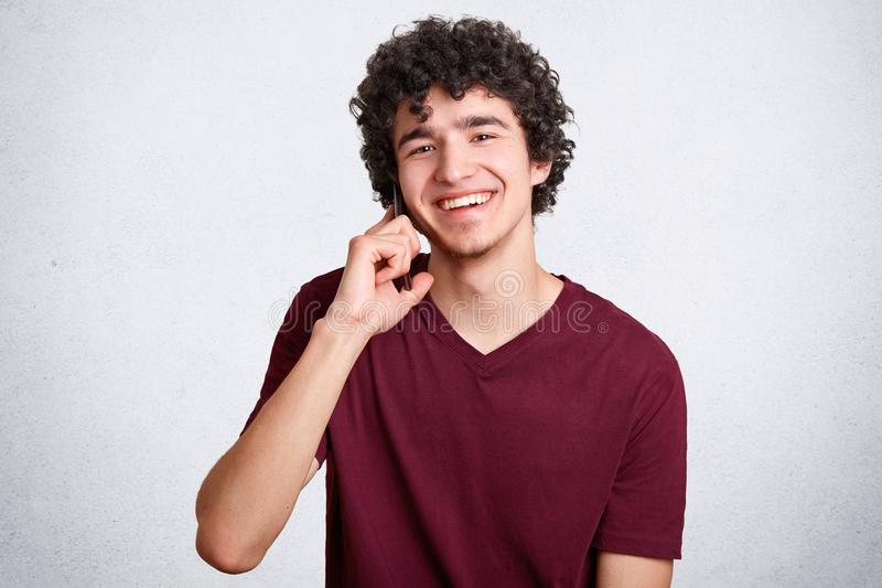 Happy teenager or hipster guy, speaks via cell phone with best friend, has delighted expression, recieves good news, smiles gently. At camera, enjoys royalty free stock photo