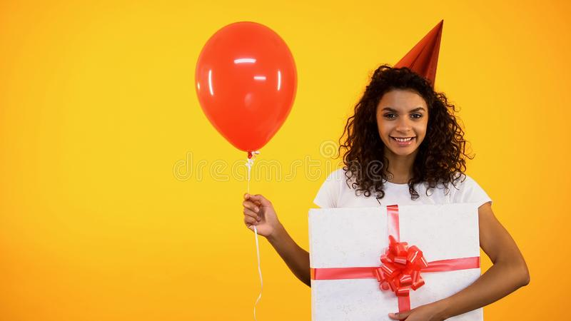 Happy teenager holding balloon and huge gift box, celebrating birthday, greeting stock photos