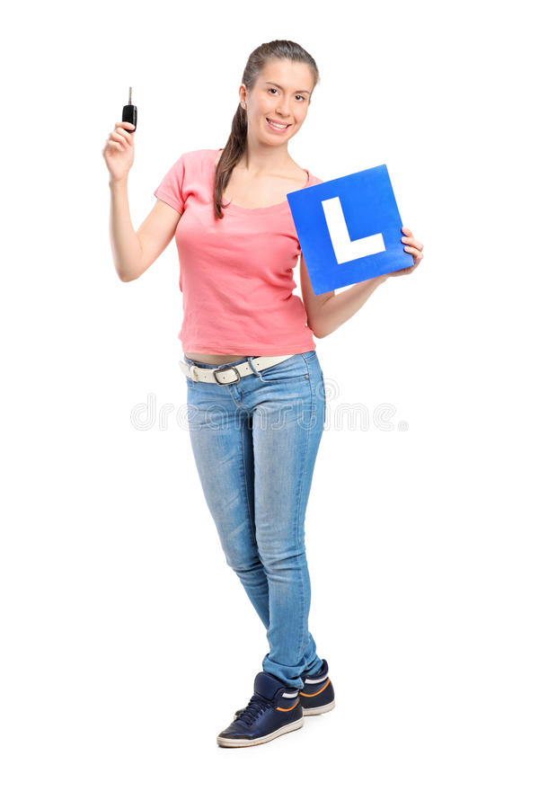 Happy teenager holding a car key and L plate royalty free stock photography