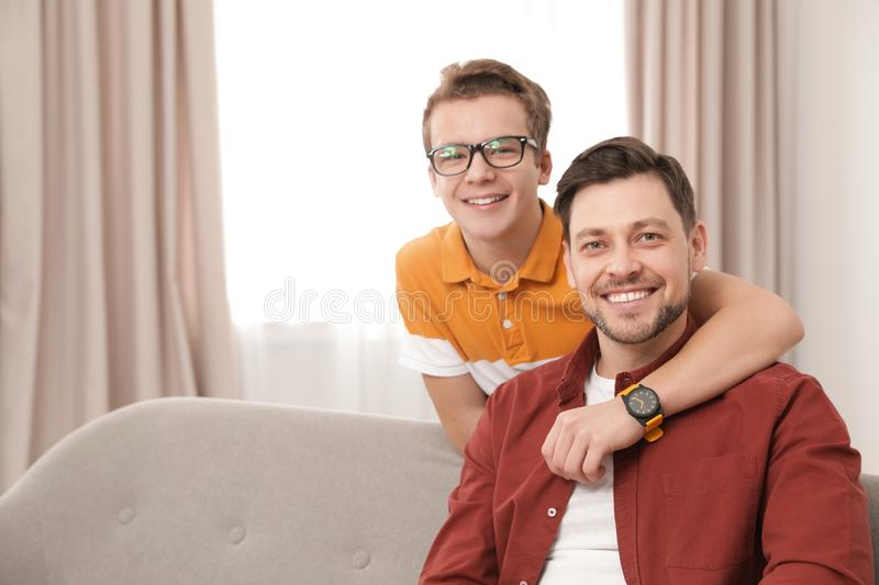 Happy teenager hugging his father at home. Space for text stock photo