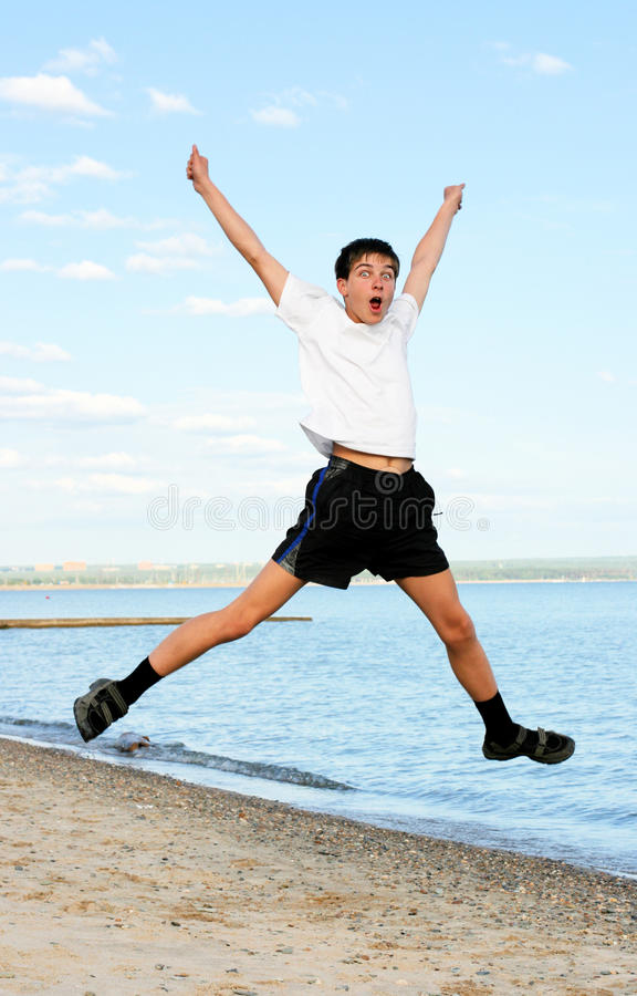 Happy teenager jumping. On the beach stock image