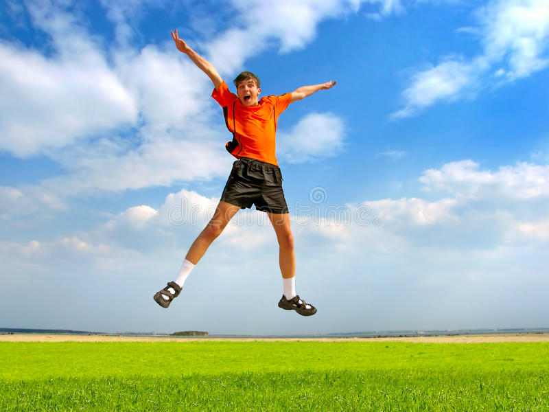 Happy teenager jumping. On the summer meadow stock photography