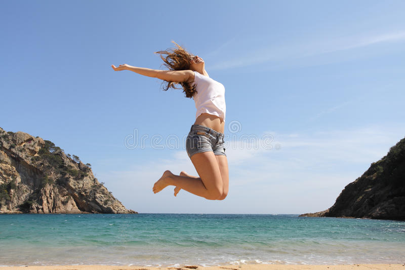 Happy teenager jumping on the beach. With the ocean in the background stock image