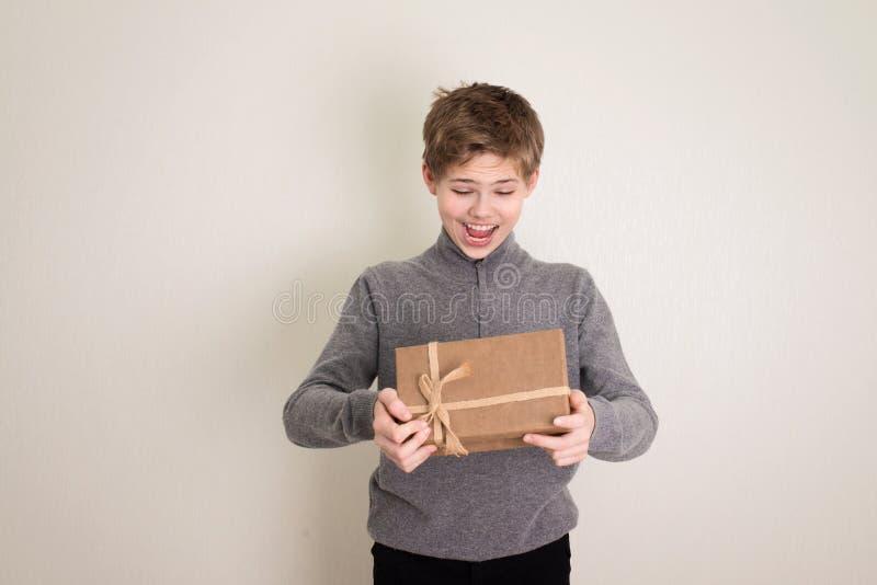 Happy Teenager Junge öffnet seine Gegenwart lizenzfreies stockbild