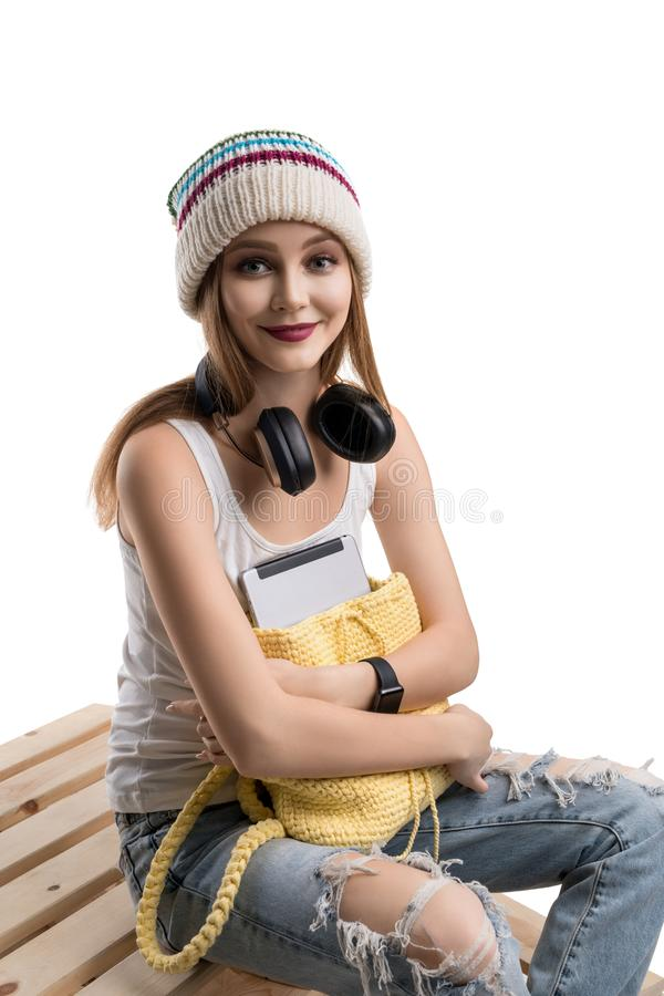 Happy teenager in knitted hat isolated shot. Young happy teenager in knitted yellow hat, white t-shirt and torn jeans sitting on wooden pallets with yellow stock photo
