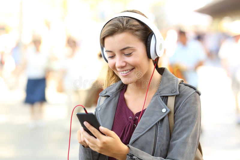 Happy teenager listening music wearing headphones stock photography