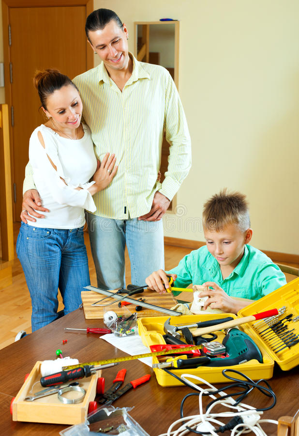 Happy teenager making something with working tools in living room royalty free stock photo