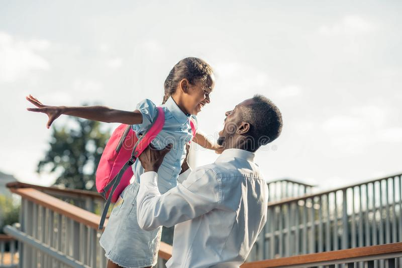 Happy teenager playing with her young daddy. Feel the moment. Strong men carrying his child while having fun during walk royalty free stock images