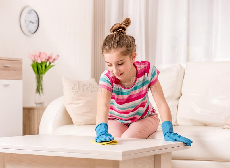 Teenager cleaning table in living room. Happy teenager in rubber gloves cleaning white table in living room royalty free stock images