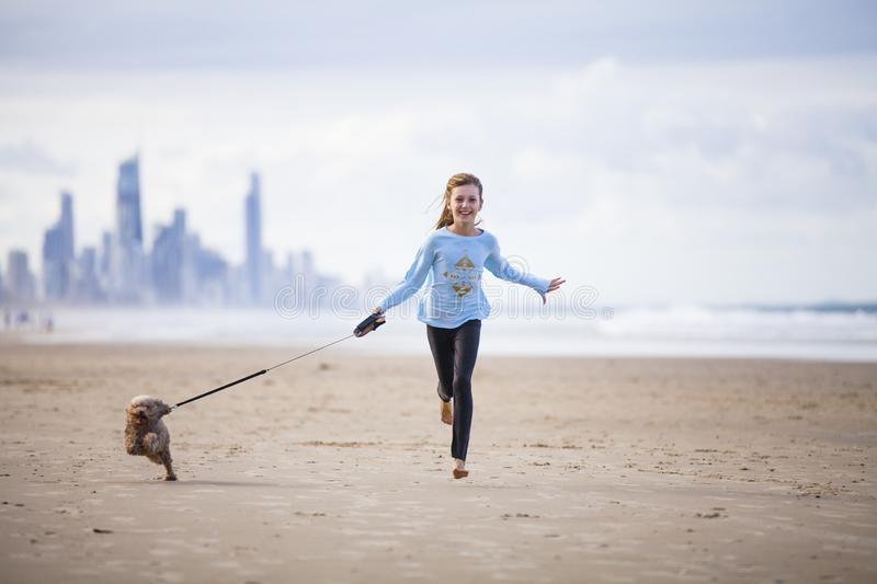Young girl with dog on lead. Happy teenager running on beach with small brown dog on a lead, background of sea and distant high rise buildings stock images