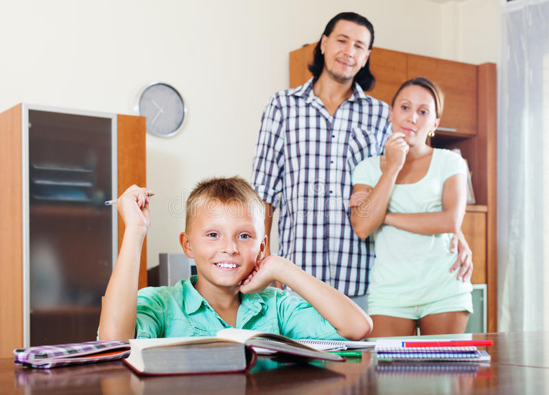 Happy teenager schoolboy doing homework. Against parents in home royalty free stock images