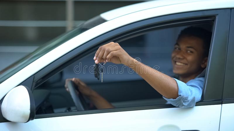 Happy teenager showing car key to window sitting on driver seat of new vehicle royalty free stock image