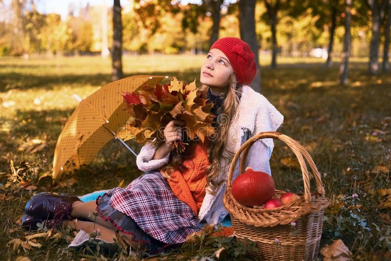 Happy teenager smiling. Autumn portrait of beautiful young girl in red hat royalty free stock images