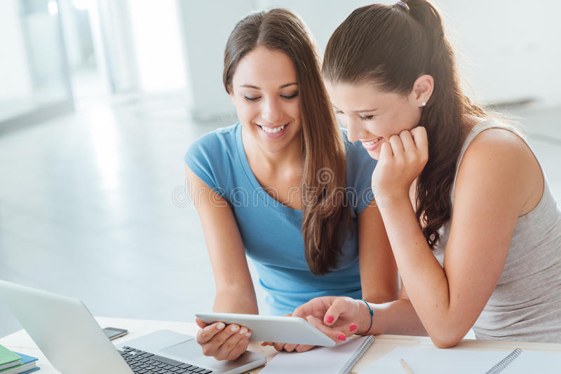 Happy teenager students using a tablet. Happy teenager students smiling and using a digital tablet at home, they are sitting at desk stock image