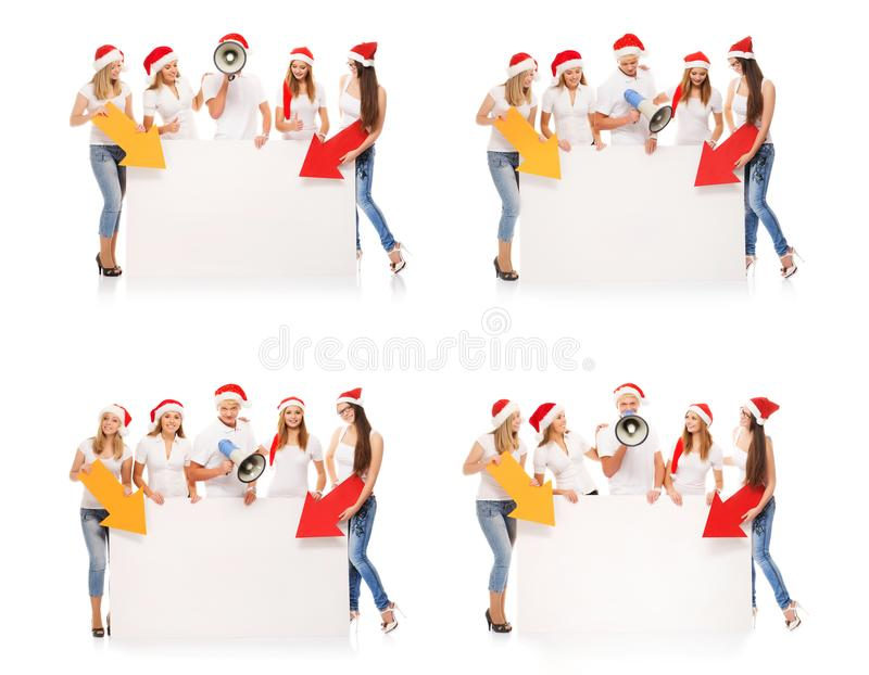 Happy teenagers in Christmas hats with white banners. A group of happy and emotional teenagers in Christmas hats are posing near a large blank banner. Collection royalty free stock photo