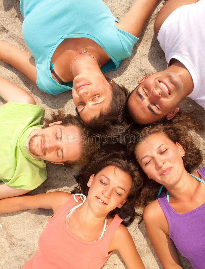 Download Happy Teenagers Lying On A Sandy Beach Stock Photo - Image: 12486060