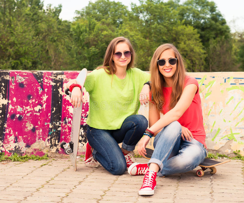 Happy teenagers outdoors. Summer. Girl friends having fun together with skate board. Urban lifestyle. royalty free stock photos