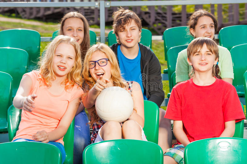 Happy teenagers sitting on the tribune during game stock photography