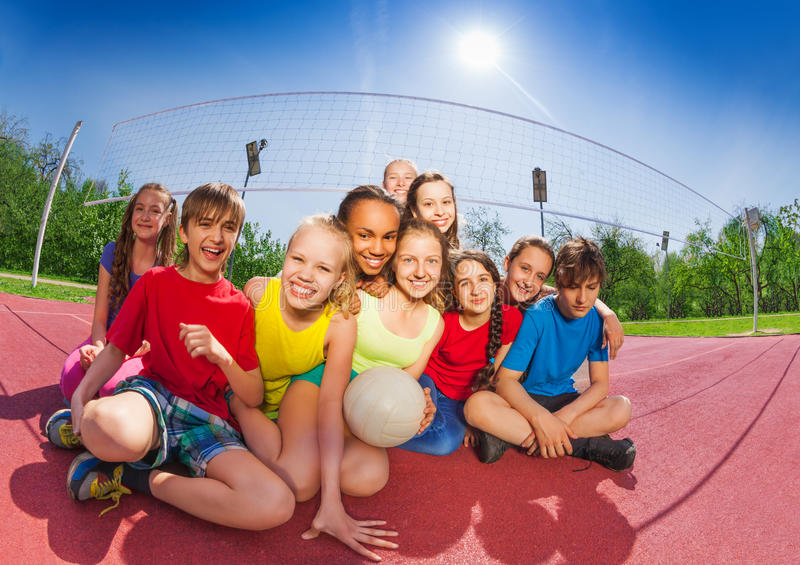 Happy teenagers sitting on volleyball court stock photos