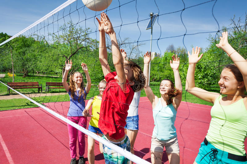 Happy teens with arms up play volleyball near net. Happy teens with arms up play volleyball near the net on the court during sunny summer day outside royalty free stock photos