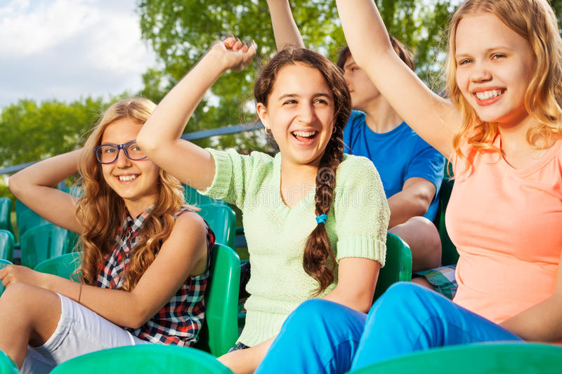 Happy teens cheering for team sitting on tribune. Happy teens cheering for the team during game at the stadium sitting on the tribune outside in summer royalty free stock photography