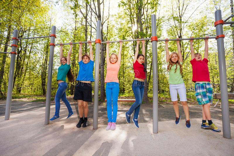 Happy teens chinning up on the playground. During summer day with trees on background royalty free stock photography