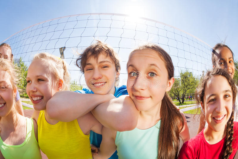 Happy teens in front of volleyball net, close-up. Fisheye close-up view of happy teens making faces standing in front of volleyball net holding ball on the game royalty free stock image