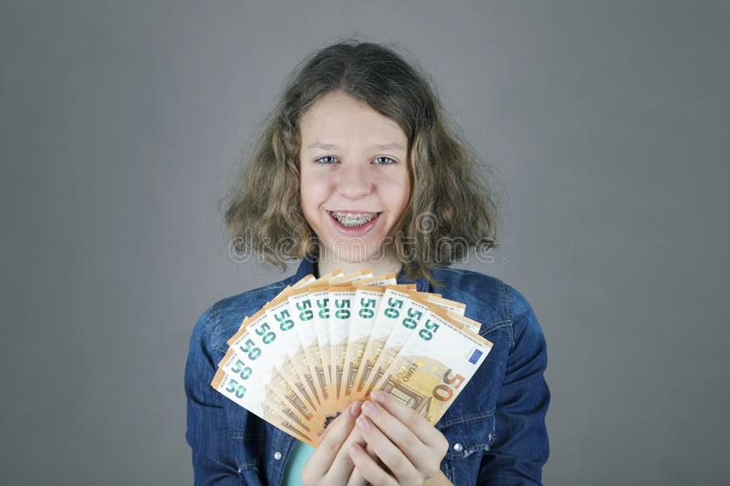 Happy teens girl holds in her hand euro. Getting money for education royalty free stock photos