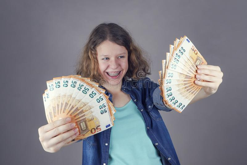 Happy teens girl holds in her hand euro. Getting money for education stock photography