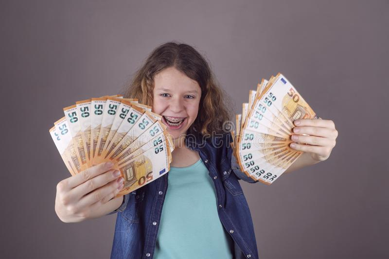 Happy teens girl holds in her hand euro. Getting money for education royalty free stock photography