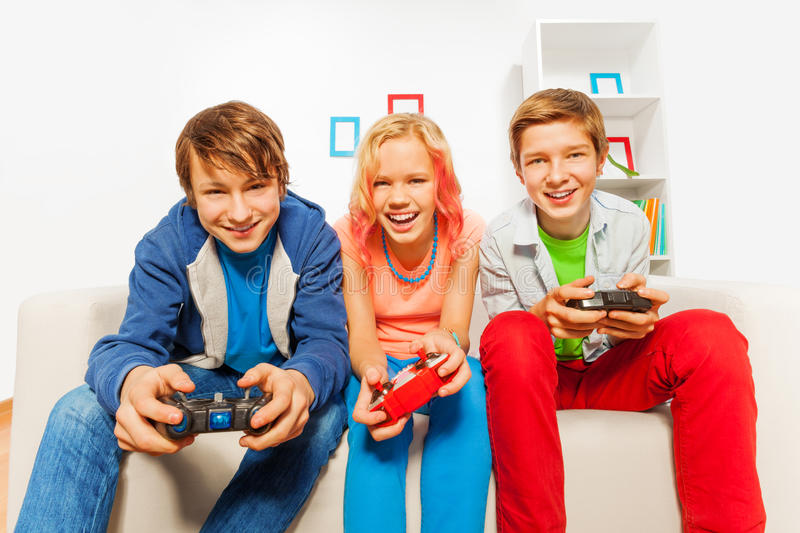 Happy teens hold joysticks and play game console. Happy teens holding joysticks and playing game console sitting on the sofa at home royalty free stock photo