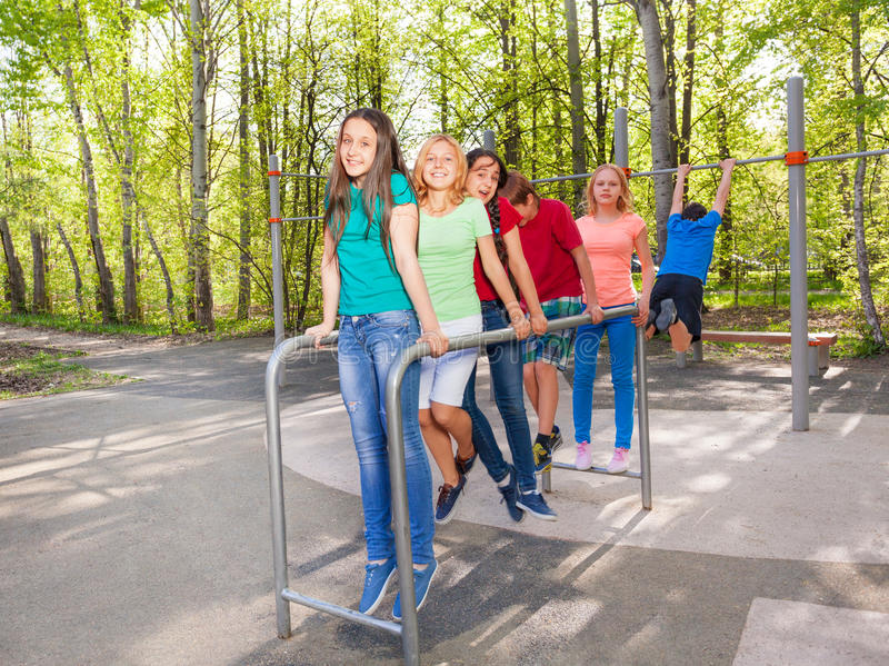 Happy teens holding and hanging on brachiating. On the playground during summer day with trees on background stock images