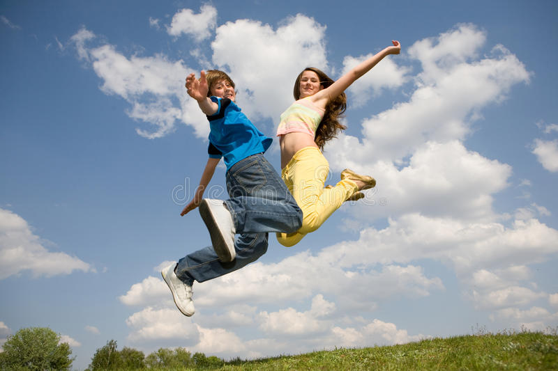 Happy teens - jumping under blue sky. Soft focus. royalty free stock photos