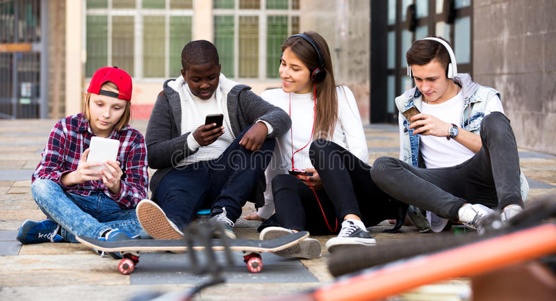 Happy teens playing on smarthphones stock photography