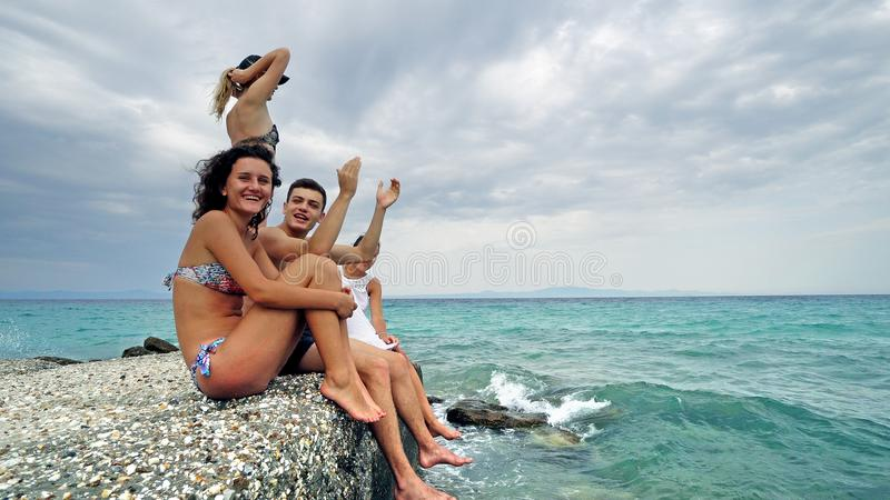 Happy teens sitting on beach pier having fun blowing kisses and waving hands. Smiling royalty free stock photos