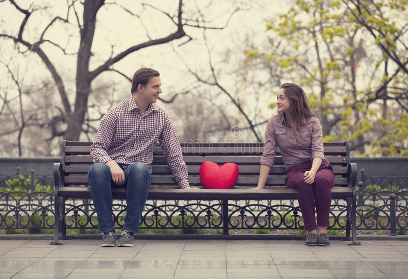 Happy teens sitting at the bench at the park.  stock images