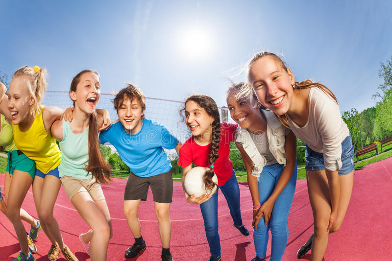 Happy teens standing on the volleyball game court. Holding ball during summer sunny day royalty free stock images