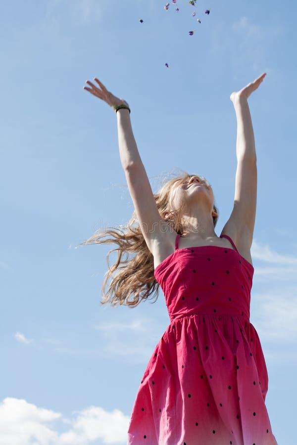 Happy Teeny Mädchen steht auf blauem Himmelshintergrund stockfotos