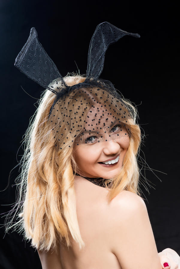 Happy temptress with hare ears on a black stock image