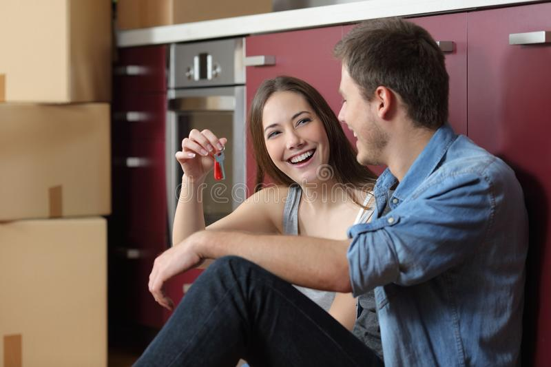 Happy tenants showing new home keys. Sitting on the floor of the kitchen stock image